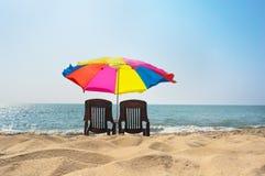 两张躺椅在海滩的一把伞下 图库摄影