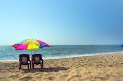 两张躺椅在海滩的一把伞下 免版税库存图片