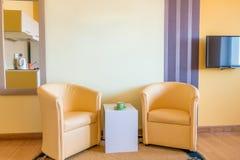 两张黄色扶手椅子和咖啡桌 库存照片