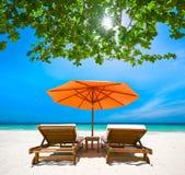 两张轻便折叠躺椅在热带海滩的一把红色伞下 库存照片
