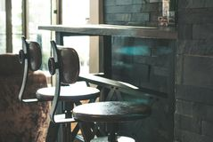 两张swirly高脚椅子安置在长的酒吧木桌下在拉特 库存图片