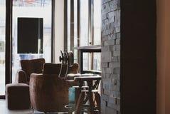 两张swirly高脚椅子安置在长的酒吧木桌下在拉特 免版税库存图片
