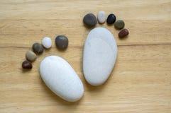 两微小的石英尺和十个脚趾在木背景,石头以一只人脚的形式 库存照片