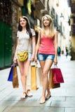 两微笑的女孩去的购物 库存照片