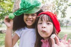 两微笑的愉快的小女孩穿戴党帽子吃糖果 库存照片