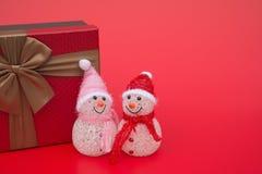 两微笑的玩具圣诞节雪人和一个当前箱子在红色背景 免版税库存图片