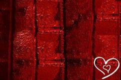 两心脏图画在红色墙壁上的为华伦泰` s天 库存图片