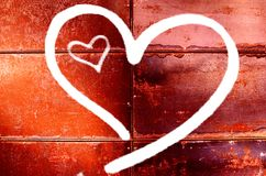 两心脏图画在红色墙壁上的为华伦泰` s天 库存照片