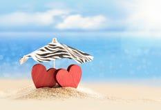 两心脏在海滩的伞下 红色上升了 免版税库存图片