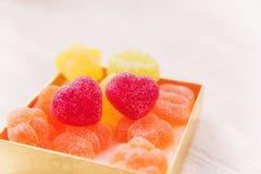 两心脏形状在金黄当前箱子的果冻糖果 白色木t 库存图片