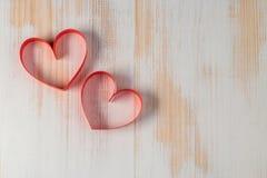 两心脏由丝带制成在木背景 免版税库存照片