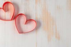 两心脏由丝带制成在木背景 免版税库存图片
