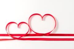 两心脏由丝带制成在白色背景 免版税图库摄影