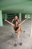 两快乐的女孩有乐趣骑马在购物车 图库摄影