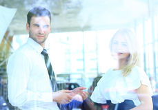 两快乐的微笑的年轻买卖人谈话在办公室 免版税库存照片