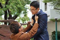 两恼怒的商人在室外公园战斗 企业冲突概念 库存图片