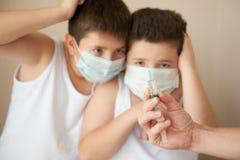 两惊吓了看起来医疗的面具的男孩手头与注射器 免版税库存图片