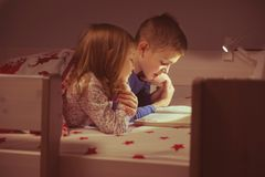 两愉快的兄弟姐妹儿童阅读书在blanke下的床上 库存图片