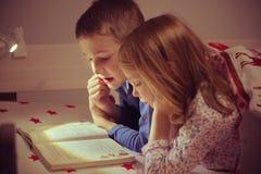 两愉快的兄弟姐妹儿童阅读书在blanke下的床上 免版税库存图片