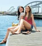 两愉快的女孩坐停泊处 库存照片