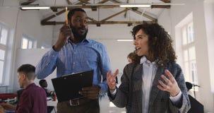 两愉快的年轻不同种族的男人和妇女,非正式地谈话公司业务的经理沿现代顶楼办公室走 股票录像