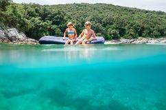 两愉快的微笑的childs坐可膨胀的木筏 库存照片