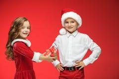 两愉快的男孩和女孩在圣诞老人帽子有礼物盒的在演播室 免版税库存照片