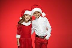 两愉快的男孩和女孩在圣诞老人帽子有礼物盒的在演播室 库存图片