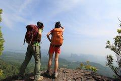 两成功的背包徒步旅行者享受看法在海边山 免版税库存照片
