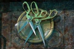 两打开了有金把柄和灰色刀片的典雅的剪刀在一个圆的铜盘,在彼此顶部的谎言,一个同步对 免版税库存图片