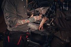 两技工审查引擎的细节,当站立在车库时的一辆残破的汽车附近 库存照片