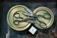 两把剪刀在圆的铜版,互相刀片的,有白色拨号盘的,原始的设计方形的古色古香的闹钟  免版税图库摄影