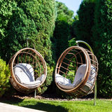 两把垂悬的椅子在一个庭院里在晴朗的夏日 免版税库存照片