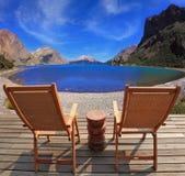 两把折叠的木椅子和山湖 库存图片