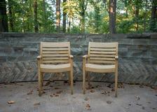 两把木胳膊椅子对石墙 免版税库存照片