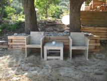 两把椅子和一张桌在沙子 免版税库存图片