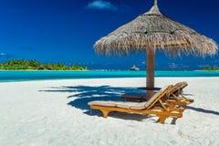 两把椅子和伞在一个海滩与阴影从棕榈树 免版税库存照片