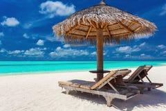 两把椅子和伞在一个热带海滩与惊人的盐水湖 免版税库存照片