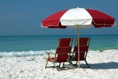 两把椅子和伞在白色沙子海滩 库存图片