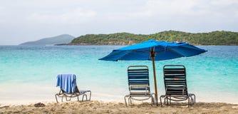 两把椅子在蓝色沙滩伞下 免版税库存照片