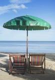 两把海滩睡椅和伞在海滩与蓝天和蓝色海视图在背景中在日落片刻,选择聚焦 库存照片