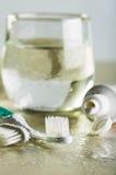 两把牙刷、牙膏和一杯在一张湿桌上的水 库存照片