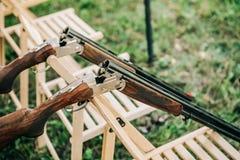两把猎枪打开被释放的安全椅子外面 免版税图库摄影