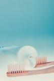 两把米黄牙齿刷子临近牙膏在蓝色白色背景的 查出 被定调子的照片 免版税库存照片