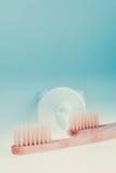 两把米黄牙齿刷子临近牙膏在蓝色白色背景的 被定调子的照片 库存图片