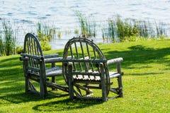 两把老木椅子在绿色草坪站立 库存图片