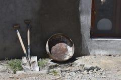 两把肮脏的大锹,一个灰色圆的碗倾斜了对村庄房子的黏土墙壁,对正确的木窗口,一白色rou 库存图片