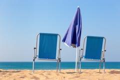 两把蓝色海滩睡椅和遮阳伞海上 库存图片