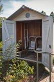两把藤条庭院椅子和在棚子存放的藤条篮子 库存照片