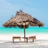 两把轻便折叠躺椅和伞在热带海滩 免版税库存照片